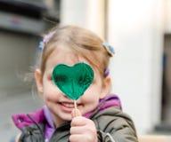 拿着心形的棒棒糖的可爱的小女孩 图库摄影
