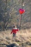 拿着心形的气球的小女孩 库存图片