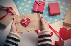 拿着心形的玩具和信封的白色白种人手  免版税库存图片