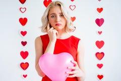 拿着心脏气球的哀伤的女孩 免版税库存图片