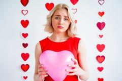 拿着心脏气球的哀伤的女孩 免版税库存照片