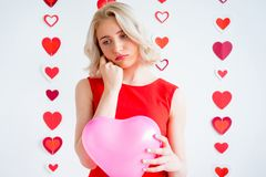 拿着心脏气球的哀伤的女孩 免版税图库摄影