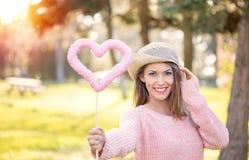 拿着心脏玩具的美丽的少妇在公园 库存照片