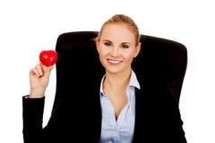 拿着心脏玩具的年轻女商人 免版税图库摄影