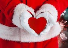 拿着心脏的圣诞老人手 免版税库存照片
