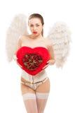 拿着心脏的天使服装的年轻白肤金发的妇女 库存图片