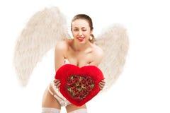 拿着心脏的天使服装的年轻白肤金发的妇女 免版税库存照片