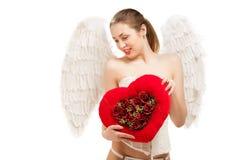 拿着心脏的天使服装的年轻白肤金发的妇女 免版税库存图片