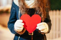 拿着心脏的女孩在情人节在冬天户外 图库摄影