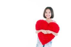 拿着心脏的愉快的亚裔逗人喜爱的女孩 免版税库存图片