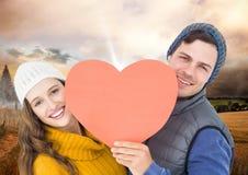 拿着心脏的浪漫夫妇反对天空背景 库存照片