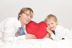 拿着心脏的父亲和儿子 免版税库存图片