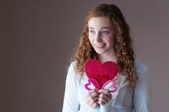 拿着心脏的青少年的女孩 图库摄影