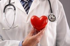 拿着心脏的医生反对胸口 免版税库存照片