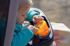 拿着快餐杯子的婴儿推车的小女孩有很多金鱼 免版税库存图片