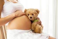 拿着怀孕的女用连杉衬裤妇女的熊 免版税库存图片