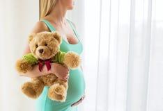 拿着怀孕的女用连杉衬裤妇女的熊 库存照片