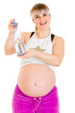 拿着怀孕的微笑的水妇女的瓶 免版税库存图片