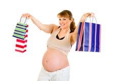 拿着怀孕的购物微笑的妇女的袋子 免版税图库摄影