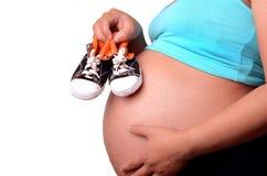 拿着怀孕的鞋子妇女的婴孩 库存图片