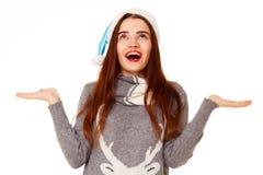 拿着您的在whi的温暖的毛线衣的年轻愉快的妇女产品 图库摄影