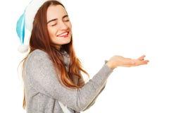 拿着您的在whi的温暖的毛线衣的年轻愉快的妇女产品 库存照片