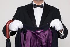 拿着您的外套和伞的男管家。 免版税库存图片