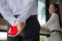 拿着惊奇的年轻人一个婚戒箱子能给一名美丽的妇女 免版税库存照片