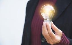 拿着想法或成功的女实业家的手电灯泡或者 免版税库存图片