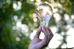 拿着想法的人的手电灯泡或成功或者太阳能 库存图片