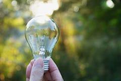 拿着想法的人的手电灯泡或成功或者太阳e 免版税库存照片