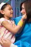 拿着愉快的女孩的护士 免版税库存图片