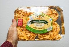 拿着意大利细面条reginelle的包裹人 免版税库存图片