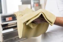 拿着意粉面团板料的厨师 库存照片