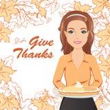 拿着感恩的微笑的妇女一个饼 免版税库存照片