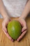 拿着成熟芒果的手在表上 库存图片