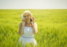 拿着我的在绿色黑麦背景的帽子的边缘白色礼服的美丽的妇女  库存照片