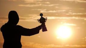 拿着战利品杯子的专业冠军挑战的剪影最佳的人优胜者奖胜利战利品顶上与 股票视频