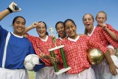 拿着战利品的女性足球队 免版税图库摄影