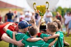 拿着战利品的年轻足球运动员 庆祝足球橄榄球冠军的男孩 免版税库存图片