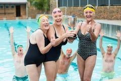 拿着战利品的资深女性游泳者在游泳池边 库存照片