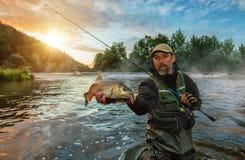 拿着战利品鱼的体育渔夫 室外渔在河 免版税库存图片