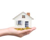 拿着房子和硬币 免版税库存图片
