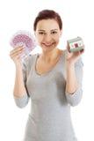 拿着房子模型和欧洲票据的愉快的妇女 免版税库存图片