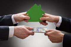 拿着房子模型和金钱的买卖人 免版税库存图片