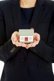 拿着房子模型的女实业家 免版税库存图片
