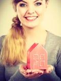 拿着房子模型的微笑的妇女 免版税库存照片