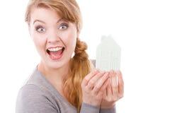 拿着房子模型的微笑的妇女 免版税库存图片