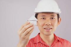 拿着房子的手有迷离工程师穿戴红色衬衣背景 免版税库存图片