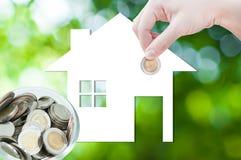 拿着房子象本质上的硬币手作为抵押的标志,自然背景的梦之家 库存图片